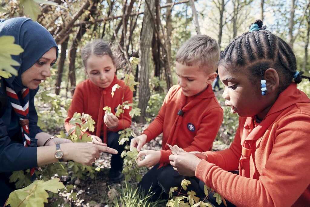 Three children in orange Squirrels uniform looking at woodland plants with a female leader wearing a headscarf